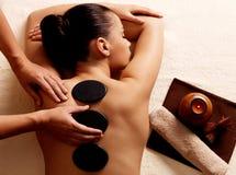 Mujer que consigue masaje de piedra caliente en salón del balneario. Imagen de archivo