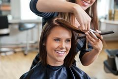 Mujer que consigue un corte de pelo imagen de archivo