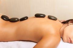 Mujer que consigue un masaje de piedra caliente en salón del balneario Imagenes de archivo