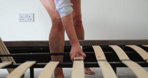 Mujer que construye un marco de la cama almacen de metraje de vídeo