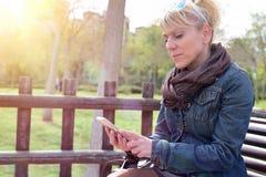 Mujer que consulta un smartphone que se sienta en un banco en parque Foto de archivo