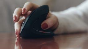 Mujer que consume el ratón ergonómico, cierre