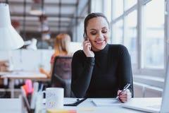 Mujer que contesta a una llamada de teléfono mientras que en el trabajo Imagen de archivo