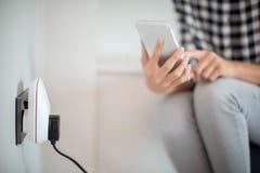 Mujer que controla el enchufe elegante usando el App en el teléfono móvil fotos de archivo