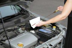 Mujer que controla el nivel 2 del motor de petróleo Imágenes de archivo libres de regalías