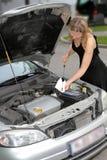 Mujer que controla el nivel de aceite de motor Imagenes de archivo