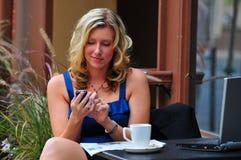 Mujer que controla para saber si hay mensajes Imagen de archivo
