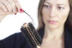 Mujer que controla si pérdida de pelo imagen de archivo