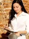 Mujer que controla una lista Fotos de archivo libres de regalías
