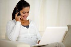 Mujer que conversa en el teléfono móvil delante del ordenador portátil Fotos de archivo libres de regalías