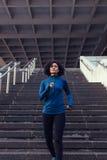 Mujer que corre abajo de las escaleras de un edificio Imágenes de archivo libres de regalías
