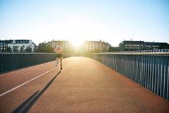 Mujer que corre abajo del puente con la sombra larga adentro detrás Imágenes de archivo libres de regalías