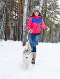 Mujer que corre con el perro en bosque del invierno Imagenes de archivo