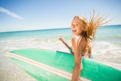 Mujer que corre con la tabla hawaiana en la playa Foto de archivo