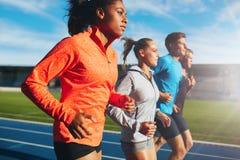 Mujer que corre con su equipo en pista Imagen de archivo