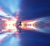Mujer que corre contra el cielo coloreado Fotos de archivo libres de regalías