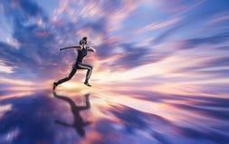 Mujer que corre contra el cielo coloreado Imagen de archivo libre de regalías