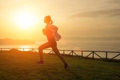 Mujer que corre contra la puesta del sol Fotografía de archivo libre de regalías