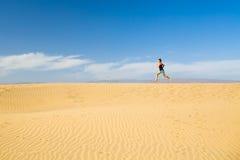 Mujer que corre descalzo en las dunas del desierto de la arena Fotos de archivo libres de regalías