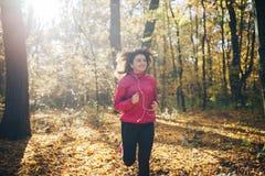 Mujer que corre durante bosque de la mañana del otoño Foto de archivo libre de regalías