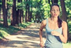Mujer que corre en auriculares que llevan del campo imágenes de archivo libres de regalías