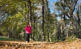 Mujer que corre en el bosque Fotografía de archivo