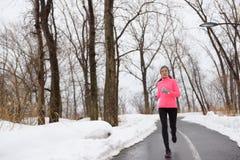 Mujer que corre en el parque nevoso de la ciudad - aptitud del invierno imagen de archivo libre de regalías