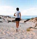 Mujer que corre en la playa imagenes de archivo