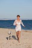 Mujer que corre en la playa con el perro casero Foto de archivo libre de regalías