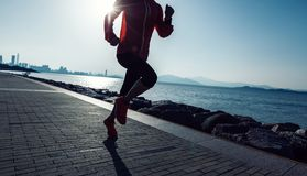 Mujer que corre en la playa de la salida del sol Imágenes de archivo libres de regalías