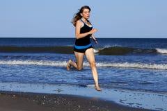 Mujer que corre en la playa descalzo Imagenes de archivo