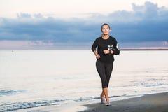 Mujer que corre en la playa en la salida del sol fotos de archivo