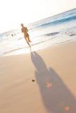 Mujer que corre en la playa en puesta del sol Imagen de archivo