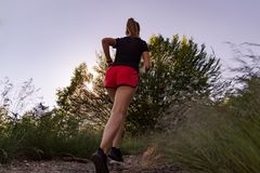 Mujer que corre en las montañas en la puesta del sol imagen de archivo