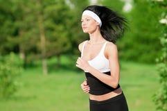 Mujer que corre en parque verde Fotografía de archivo libre de regalías