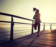 mujer que corre en paseo marítimo de la playa durante salida del sol Foto de archivo libre de regalías