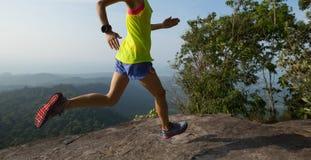 Mujer que corre en pico de montaña imagen de archivo libre de regalías