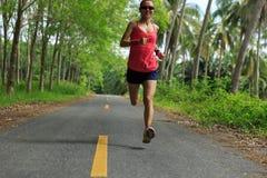 Mujer que corre en rastro tropical del bosque de la mañana Fotografía de archivo
