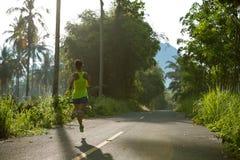 Mujer que corre en rastro tropical del bosque de la mañana Imagen de archivo libre de regalías