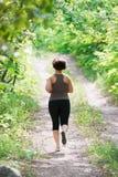 Mujer que corre en un camino del parque, al aire libre activando imagen de archivo