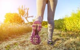 Mujer que corre en un campo Fotos de archivo libres de regalías