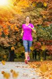 Mujer que corre en un parque durante tiempo del otoño imagenes de archivo