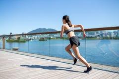 Mujer que corre en una ciudad Foto de archivo libre de regalías