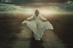 Mujer que corre libremente en una tierra solitaria Imagen de archivo libre de regalías