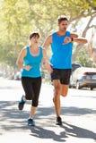 Mujer que corre a lo largo de la calle con el instructor personal imágenes de archivo libres de regalías