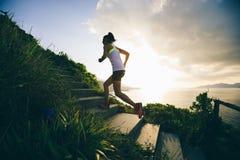 Mujer que corre para arriba en las escaleras de la montaña de la playa fotos de archivo libres de regalías