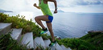 Mujer que corre para arriba en las escaleras de la montaña de la playa fotografía de archivo libre de regalías