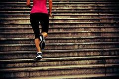 Mujer que corre para arriba en las escaleras de piedra Imagen de archivo libre de regalías