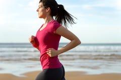 Mujer que corre en la playa Imagen de archivo
