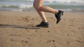 Mujer que corre solamente en la puesta del sol hermosa en la playa metrajes